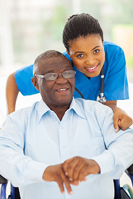 beautiful young black female caregiver in bright blue scrubs hugging elderly black man sitting in a wheelchair