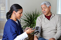black female caregiver in bright blue scrubs doing a blood pressure check on an elderly black man