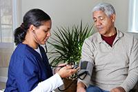 black female caregiver in bright blue scrubs doing a blood pressure check on an elderly black man