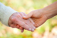 showing a closeup of an elderly hand and a young adult hand as they hold hands together